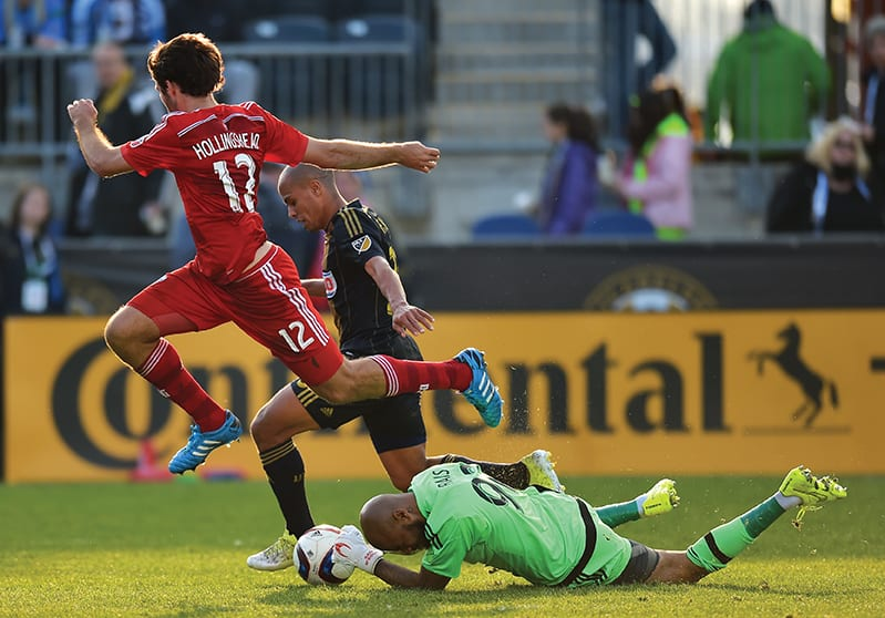 CHESTER, PA - MARCH 21: Ryan Hollingshead #12 of FC Dallas jumps over Rais Mbolhi #92 of Philadelphia Union as he makes a save and teammate Fabinho #33 tries to defend at PPL Park on March 21, 2015 in Chester, Pennsylvania. Dallas won 2-0. (Photo by Drew Hallowell/Getty Images)